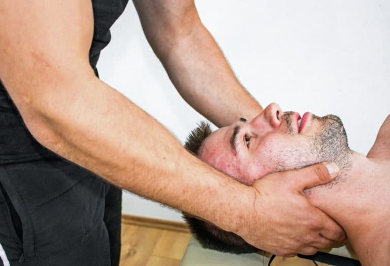 . Personal trainer working on a man's neck as part of a rehabilitation therapy
