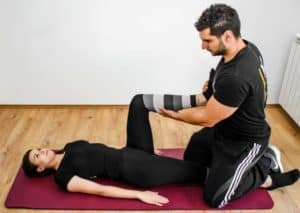 Man and woman doing stretching exercises on a yoga mat.